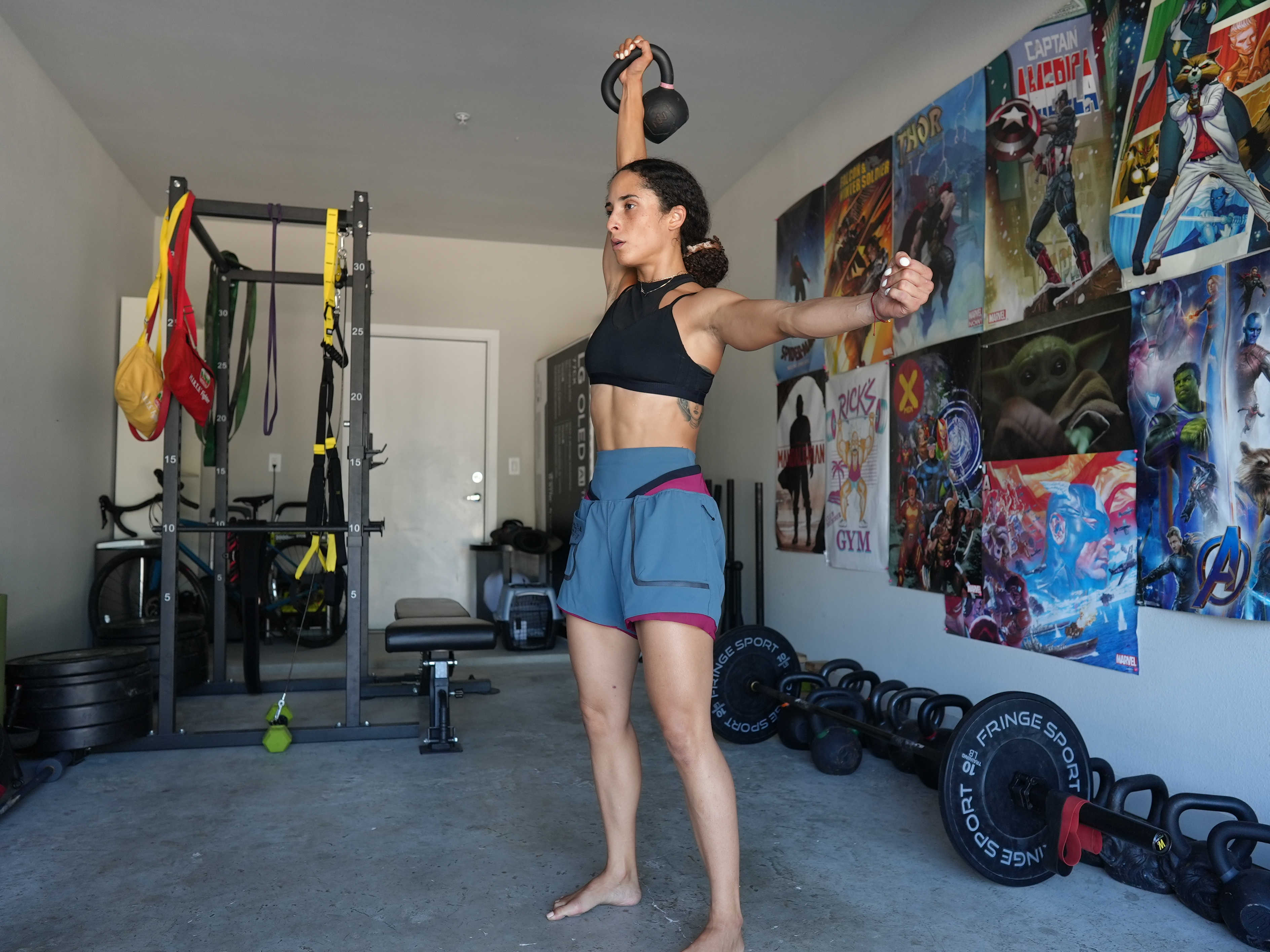 Woman stands in a workout room unilaterally lifting a kettle bell above her head.