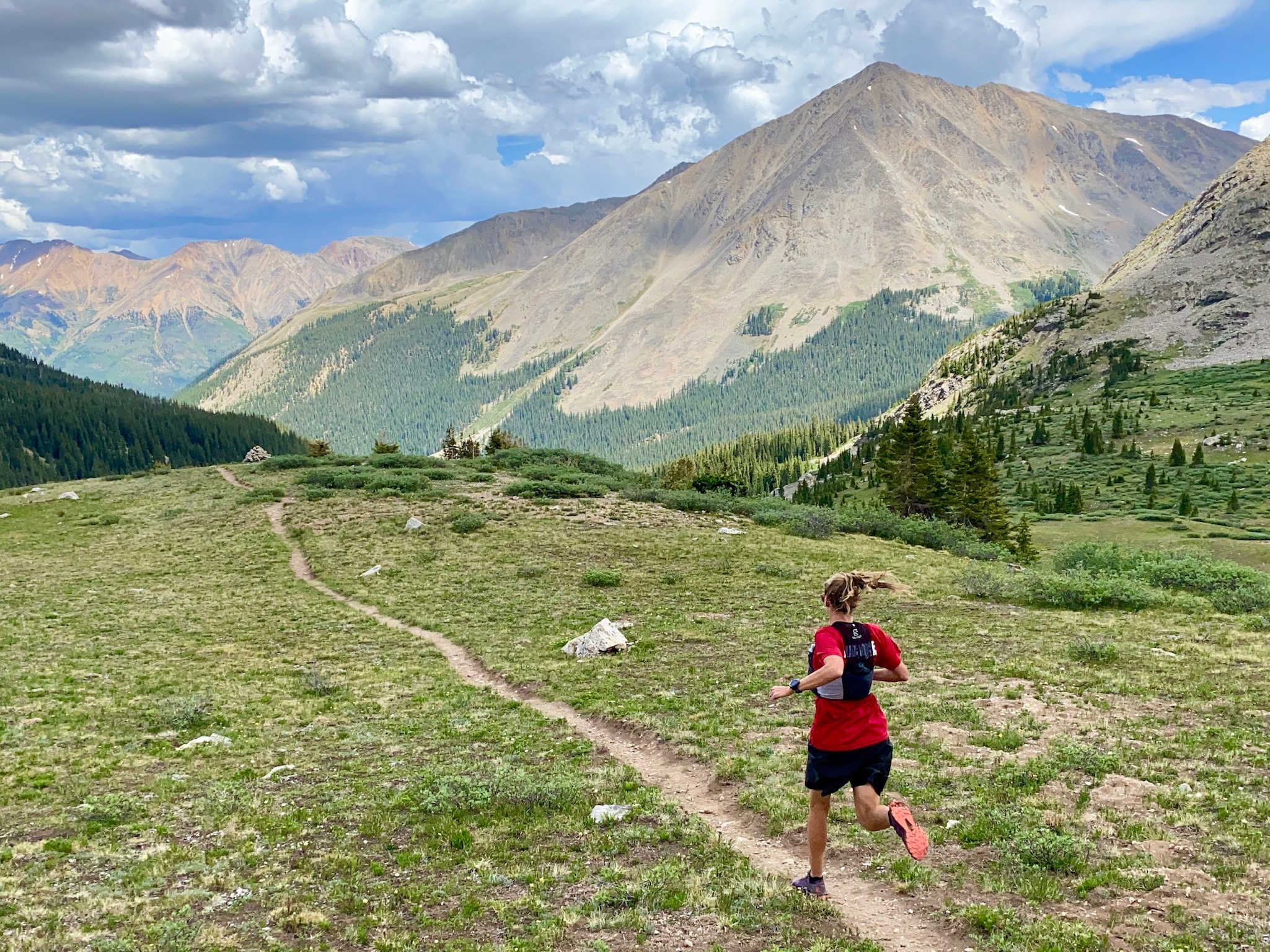 Superfeet Ambassador Courtney Dauwalter runs along a trail with an awe-inspiring view