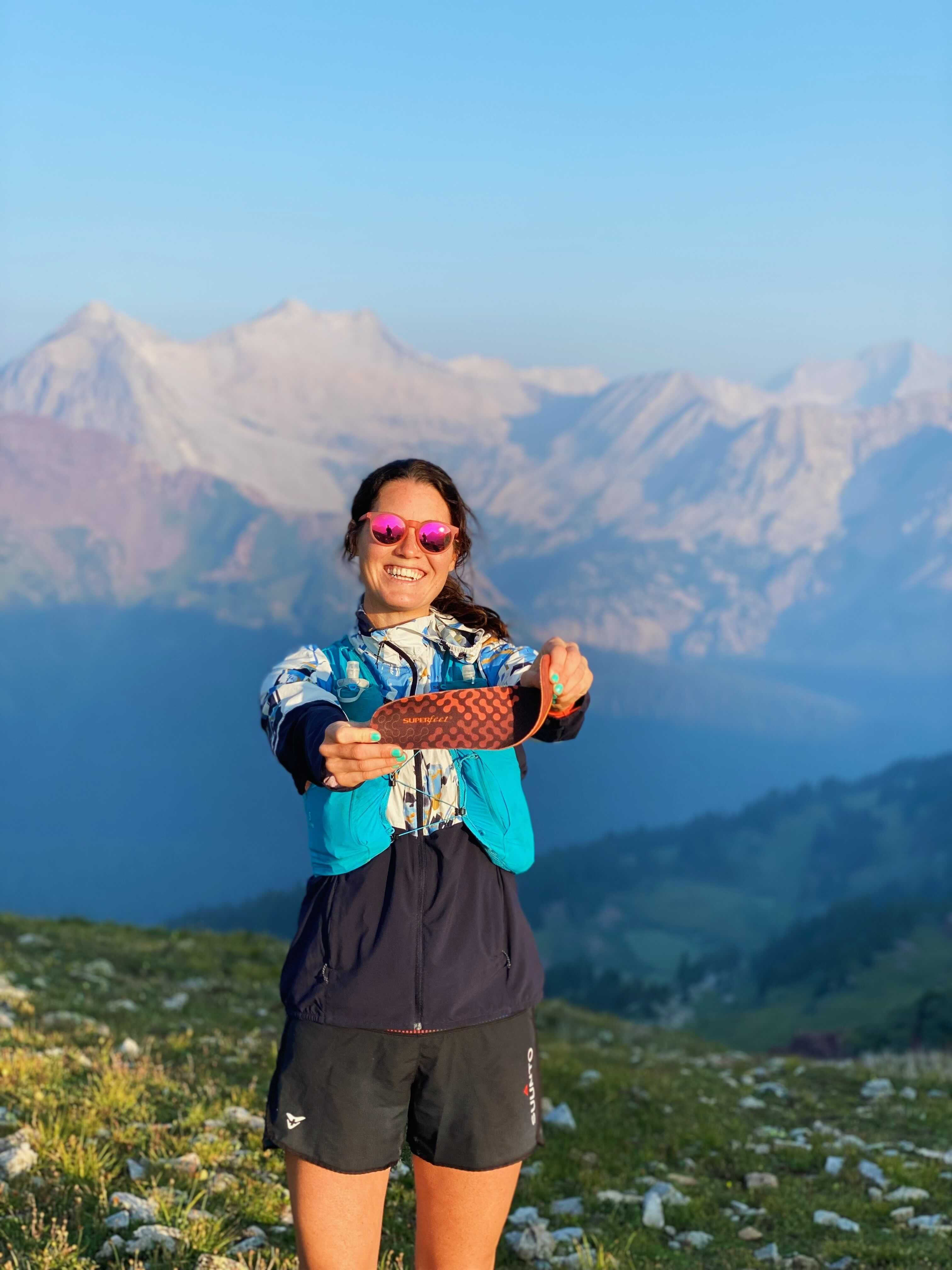 A trail runner holds out a Superfeet ADAPT Running insole in front of a stunning mountain backdrop