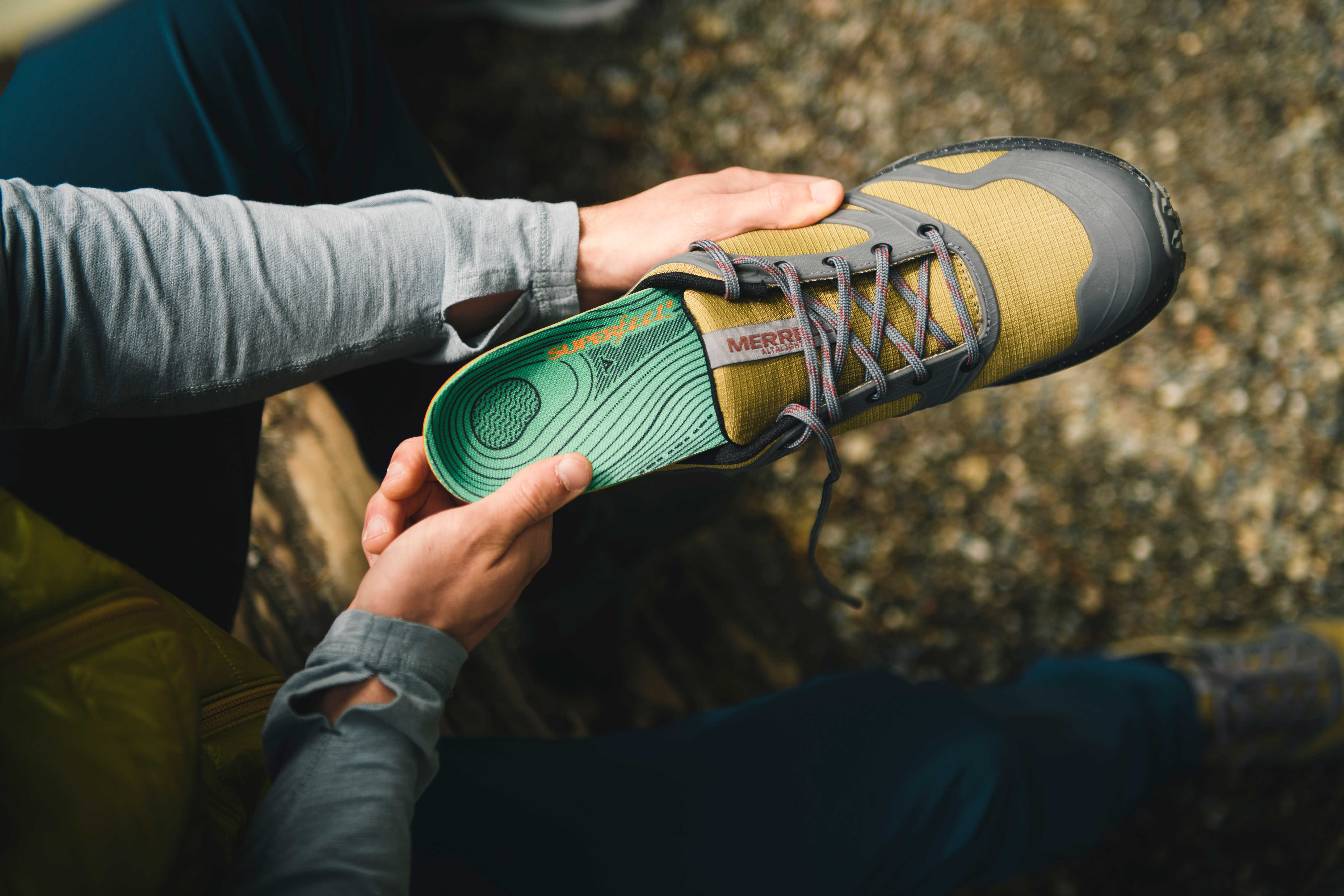 Superfeet green hiking insole being put into a pair of outdoor hiking shoes