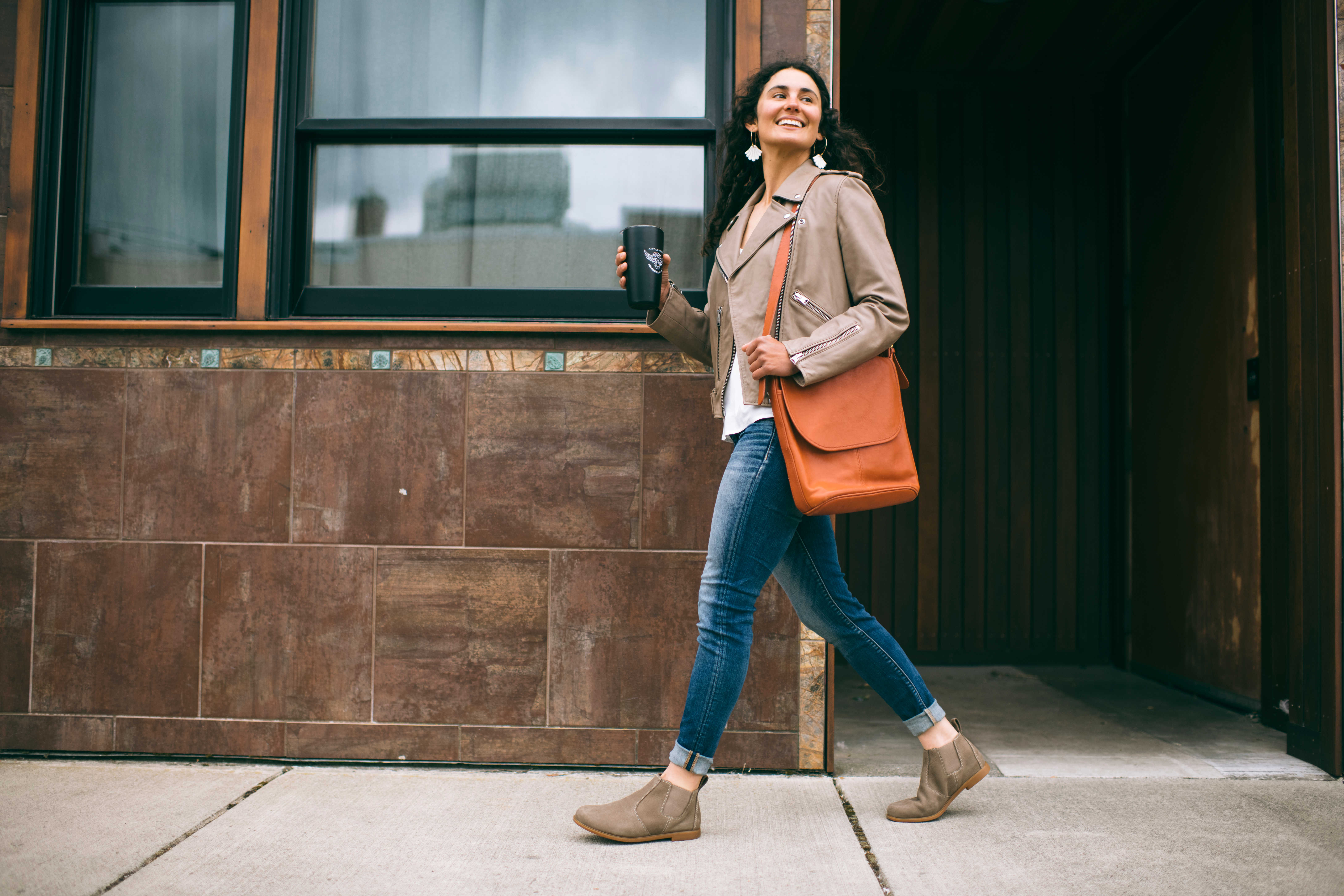 Woman smiles as she walks down a city street holding a cup of coffee