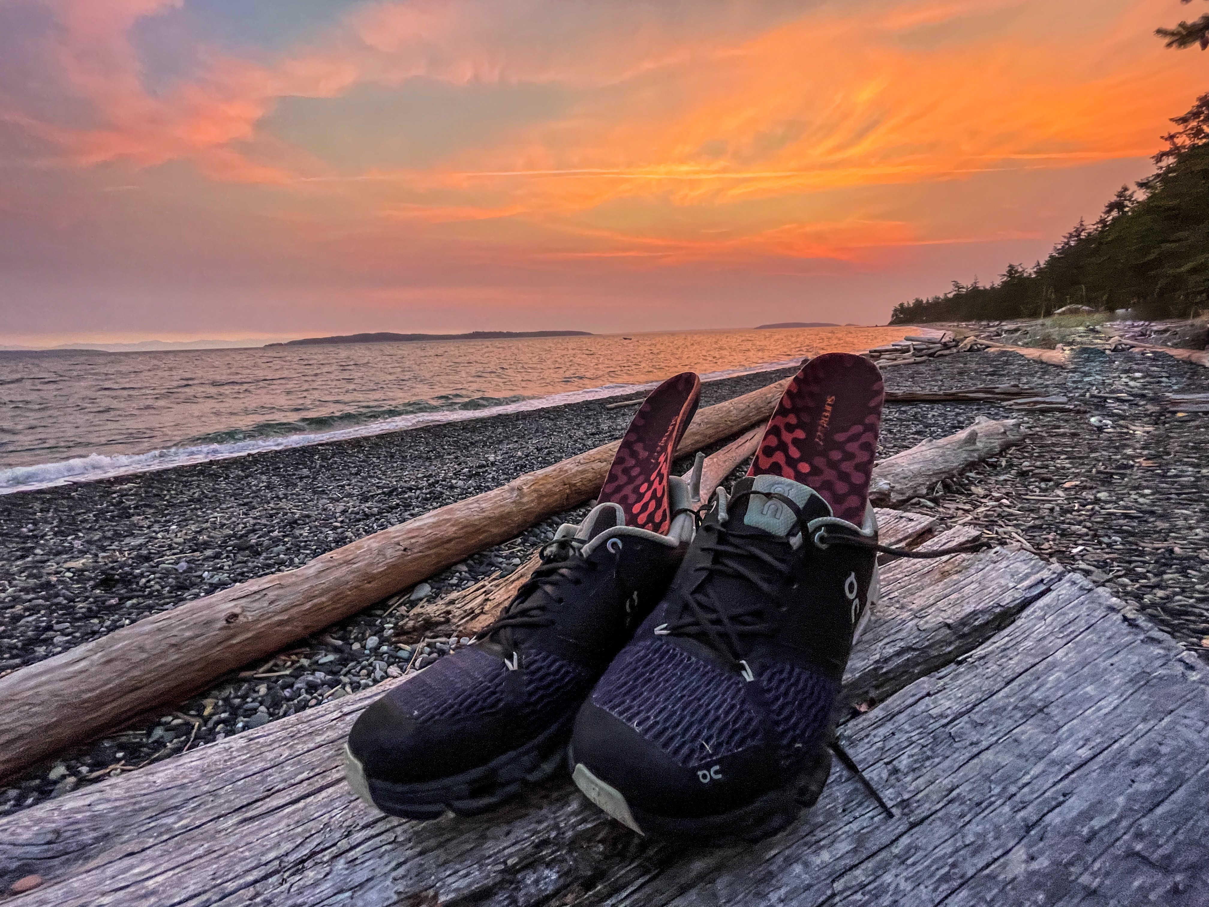 ADAPT Running Insoles in a pair of On running shoes set on a Pacific Northwest rocky beach at sunset